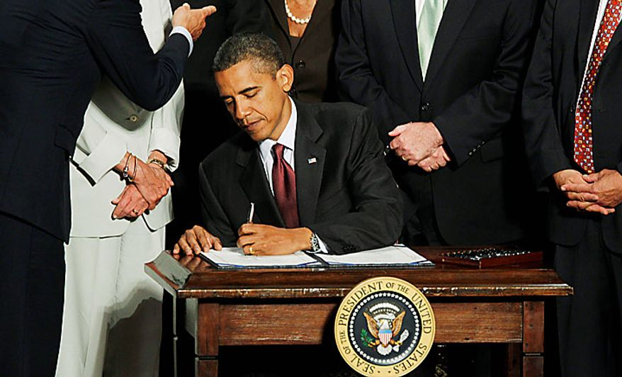 President Obama signs the Dodd-Frank Wall Street Reform and Consumer Protection Act at the Ronald Reagan Building and International Trade Center in Washington on Wednesday, July 21, 2010. (AP Photo/Charles Dharapak)