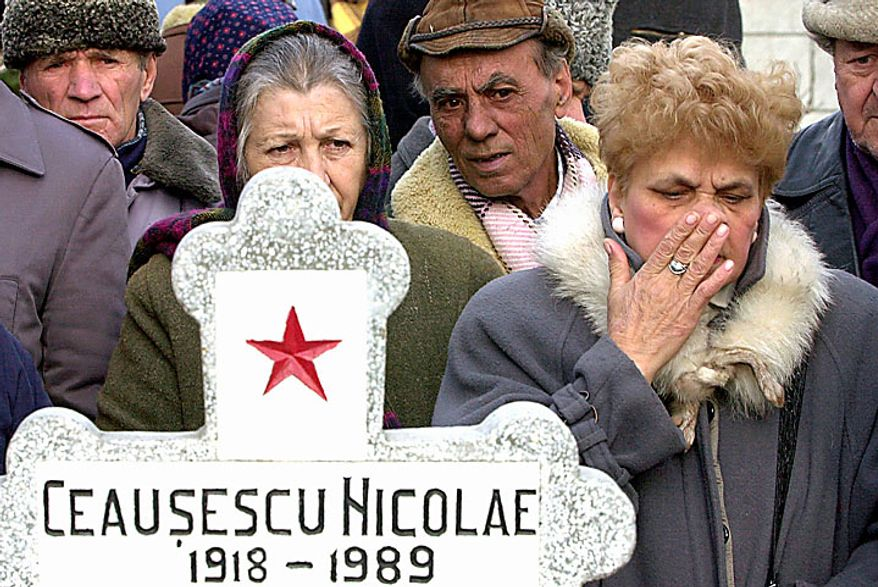 In this photo taken on Jan. 26, 2001, Romanians stand behind the cross at the presumed grave of former communist dictator Nicolae Ceausescu during a commemoration of his 83rd birthday in Bucharest, Romania. Taking the country by surprise, forensic scientists on Wednesday, July 21, 2010, exhumed what are believed to be the bodies of Ceausescu and his wife, Elena, at the request of their children. (AP Photo/Vadim Ghirda, File)