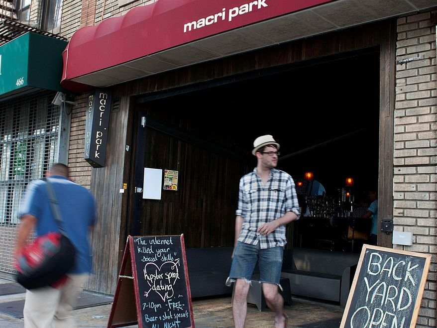 """A hipster walks by the Macri Park bar in the Williamsburg section of the New York borough of Brooklyn. The bar is one venue that hosts """"hipster speed dating,"""" where groups of people have microdates at events such as """"The Internet Killed Your Social Skills."""" (Associated Press)"""