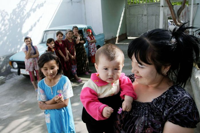 An Uzbek woman walks with her children in Ferghana, Uzbekistan. According to rights groups, victims and health officials, hundreds of Uzbek women have been surgically sterilized without their knowledge in a program looking to curb overpopulation. (Associated Press)