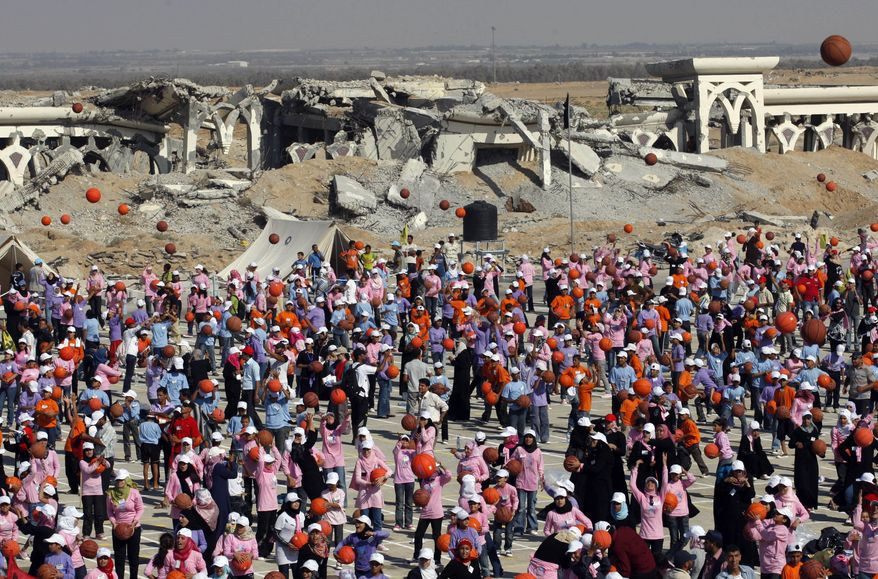 Thousands of Palestinian children throw basketballs to the air to celebrate their attempt to break the world record for the number of basketballs bounced simultaneously in the destroyed Gaza international airport in Rafah southern Gaza Strip, Thursday, July 22, 2010. The top U.N. aid official says more than 7,000 Gaza children have simultaneously dribbled basketballs for five minutes in an attempt to enter the Guinness Book of World Records. (AP Photo/Khalil Hamra)