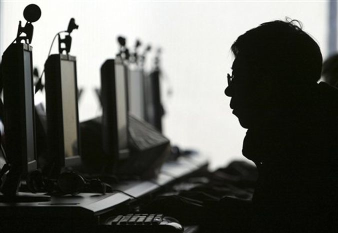FILE - In this Jan 23, 2008 file photo, a computer user is silhouetted with a row of computer monitors at an Internet cafe in Shenyang, in northern China's Liaoning province. Word leaked out slowly, spread by tech-savvy folks on Twitter: Internet porn is now openly available in China. Is the new access to online pornography a policy change or a trap? It throws into sharp relief what many see as the main mission of China's aggressive Internet censorship: blocking content that might challenge the political authority of the communist government. (AP Photo/File)