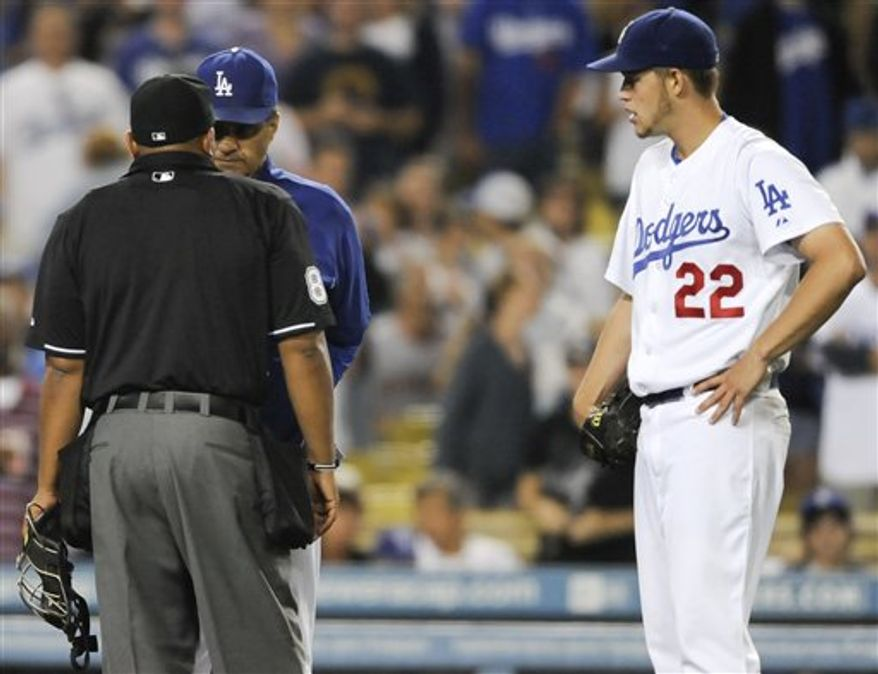 Los Angeles Dodgers manager Joe Torre, back center, talks with home plate umpire Adrian Johnson after ejecting Los Angeles Dodgers starting pitcher Clayton Kershaw (22) in the seventh inning of a baseball game against the San Francisco Giants, Tuesday, July 20, 2010, in Los Angeles. (AP Photo/Gus Ruelas)