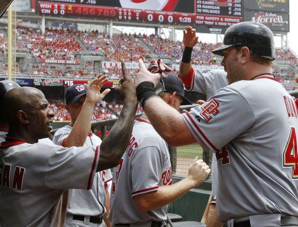 ASSOCIATED PRESS Washington Nationals' Adam Dunn, right, is congratulated by Nyjer Morgan, left, after Dunn hit a two-run home run off Cincinnati Reds starting pitcher Edinson Volquez in the third inning of a baseball game, Thursday, July 22, 2010, in Cincinnati.