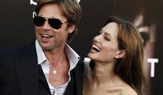 """Cast member Angelina Jolie, right and Brad Pitt arrive at the premiere of """"Salt"""" in Los Angeles, on Monday, July 19, 2010.  (AP Photo/Matt Sayles)"""