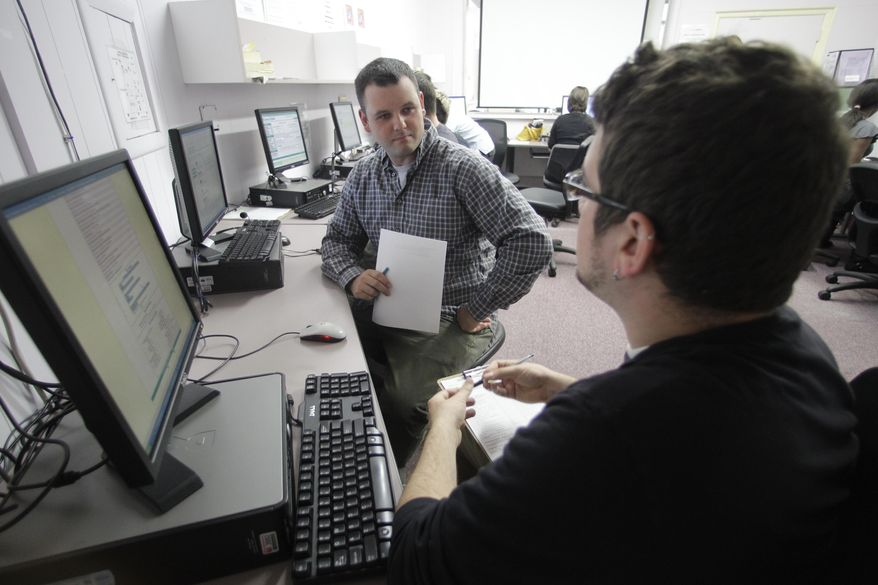 Eric Bilderback (left) holds his resume as he talks with Mike Watson, a business employment specialist at WorkSource Oregon, on Tuesday, July 20, 2010, in Portland, Ore. Congress approved a bill on Thursday, July 22, 2010, that extends unemployment benefits for an estimated 2.5 million Americans. (AP Photo/Rick Bowmer)