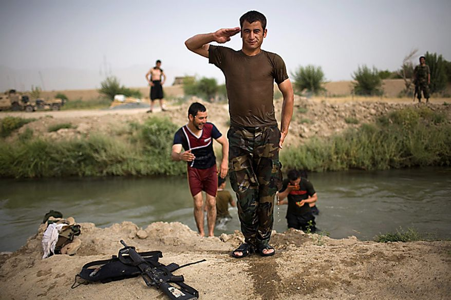 An Afghan army soldier poses after swimming in a canal near the joint Afghan-U.S. base COP Nolen, in the volatile Arghandab Valley, Kandahar, Afghanistan, Thursday, July 22, 2010. (AP Photo/Rodrigo Abd)