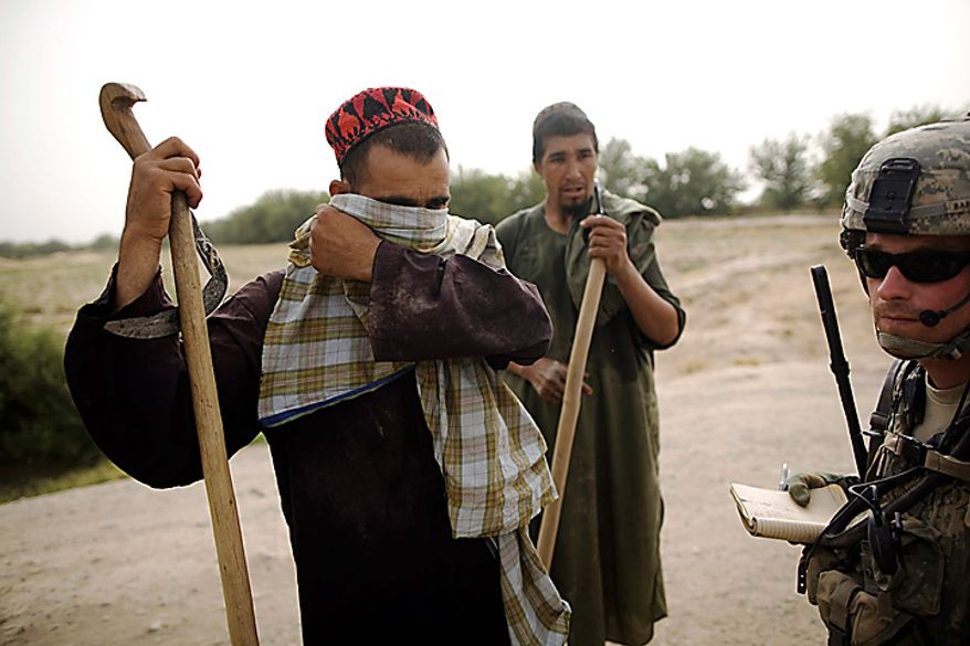 An Afghan villager describes how insurgents disguise themselves as he speaks with U.S. Army 1st Lt. Christopher Babcock, from New Orleans, La., at COP Nolen, in the volatile Arghandab Valley, Kandahar, Afghanistan, Thursday, July 22, 2010. (AP Photo/Rodrigo Abd)