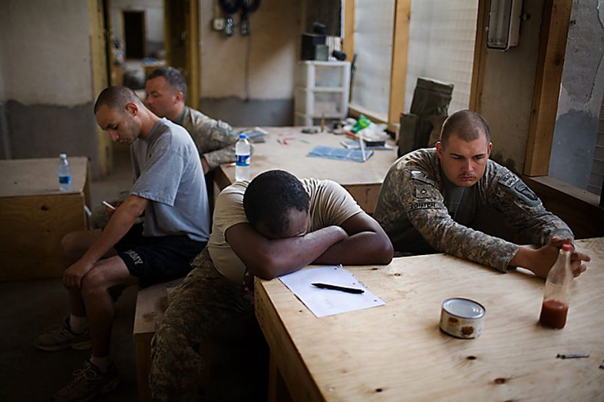 U.S. Army soldiers of the 1st Battalion 320th Alpha Battery, 2nd Brigade of the 101st Airborne Division, relax after a morning exercise session at Combat Outpost Nolen, in the volatile Arghandab Valley, in Kandahar, Afghanistan, Thursday, July 22, 2010. (AP Photo/Rodrigo Abd)