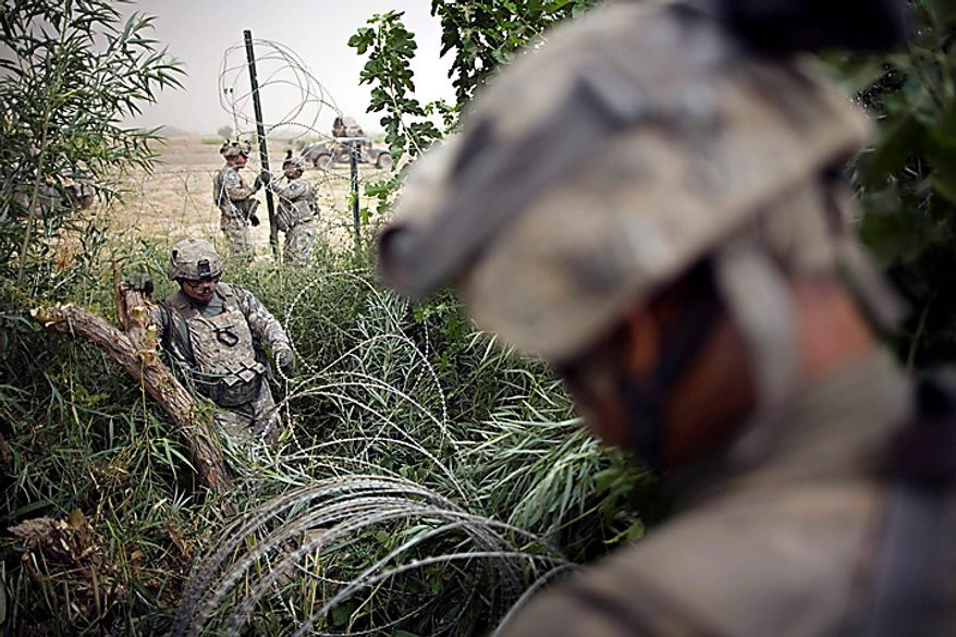 U.S. Army soldiers of the 1st Battalion 320th Alpha Battery, 2nd Brigade of the 101st Airborne Division, lay razor wire outside the walls of Combat Outpost Nolen, in the volatile Arghandab Valley, in Kandahar, Afghanistan, Thursday, July 22, 2010. (AP Photo/Rodrigo Abd)