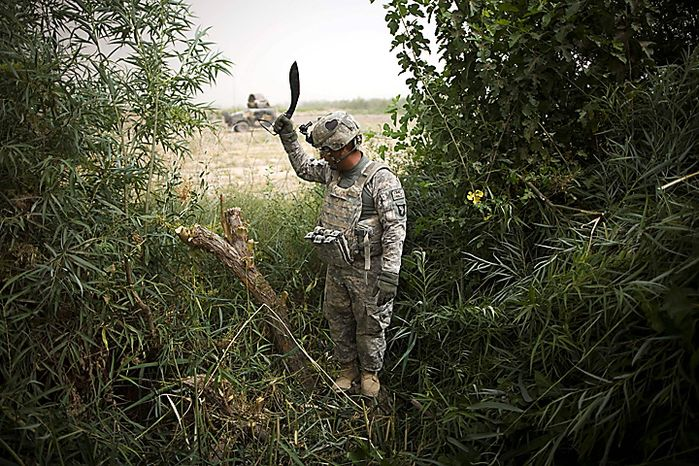 A U.S. Army soldier of the 1st Battalion 320th Alpha Battery, 2nd Brigade of the 101st Airborne Division, clears undergrowth to lay protective razor wire outside the walls of Combat Outpost Nolen, in the volatile Arghandab Valley, in Kandahar, Afghanistan, Thursday, July 22, 2010. (AP Photo/Rodrigo Abd)