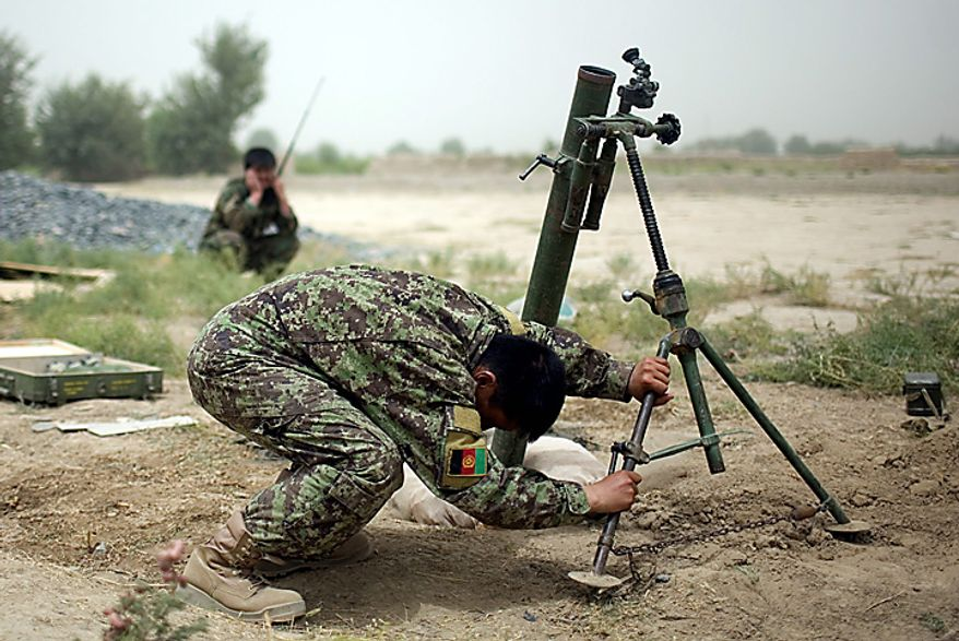 An Afghan army soldier ducks after firing a 60 mm mortar at insurgent positions in a village near Combat Outpost Nolen, in the volatile Arghandab Valley, in Kandahar, Afghanistan, Thursday, July 22, 2010. (AP Photo/Rodrigo Abd)