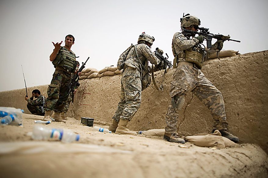 US Army soldiers of the 1st Battalion 320th Alpha Battery, 2nd Brigade of the 101st Airborne Division, search for insurgents from a rooftop firing position at Combat Outpost Nolen, in the volatile Arghandab Valley, in Kandahar, Afghanistan, Thursday, July 22, 2010. (AP Photo/Rodrigo Abd)