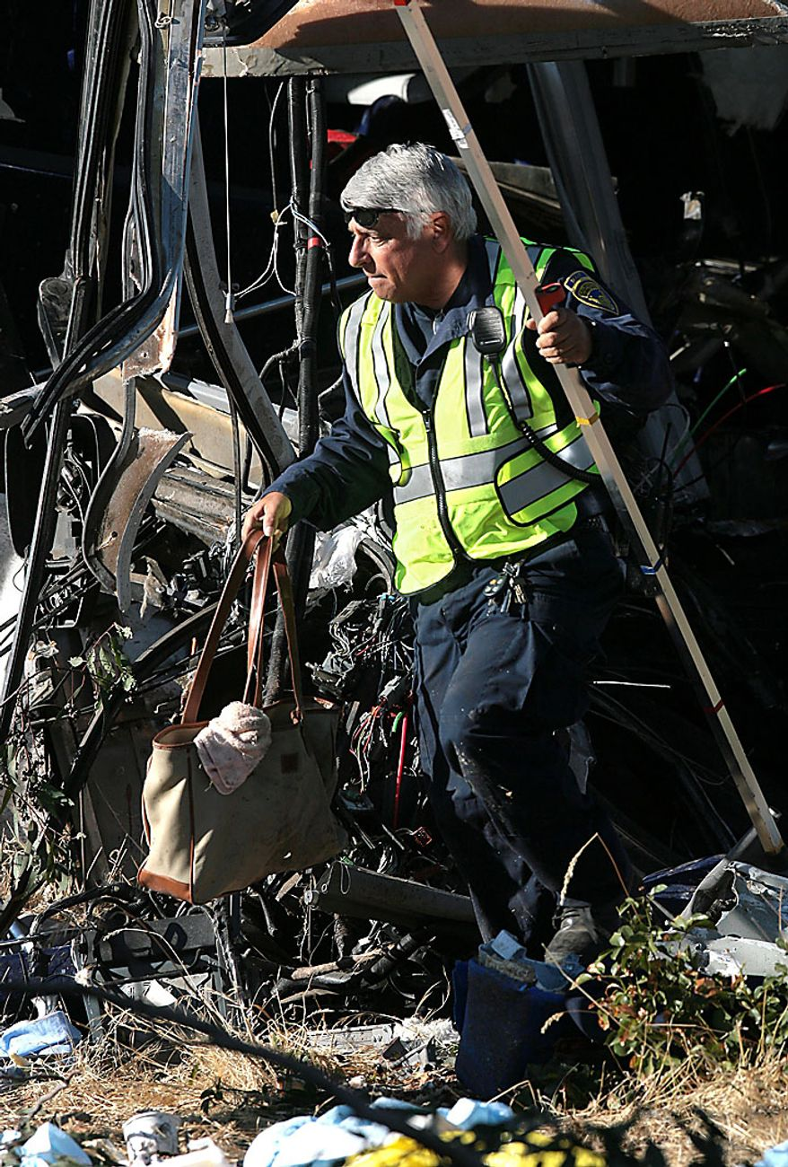 A California Highway Patrol investigator retrieves a handbag from the wreckage of the fatal Greyhound bus accident in which at least six people were killed and others injured on Thursday, July 22, 2010, in Fresno, Calif. (AP Photo/The Fresno Bee, John Walker)