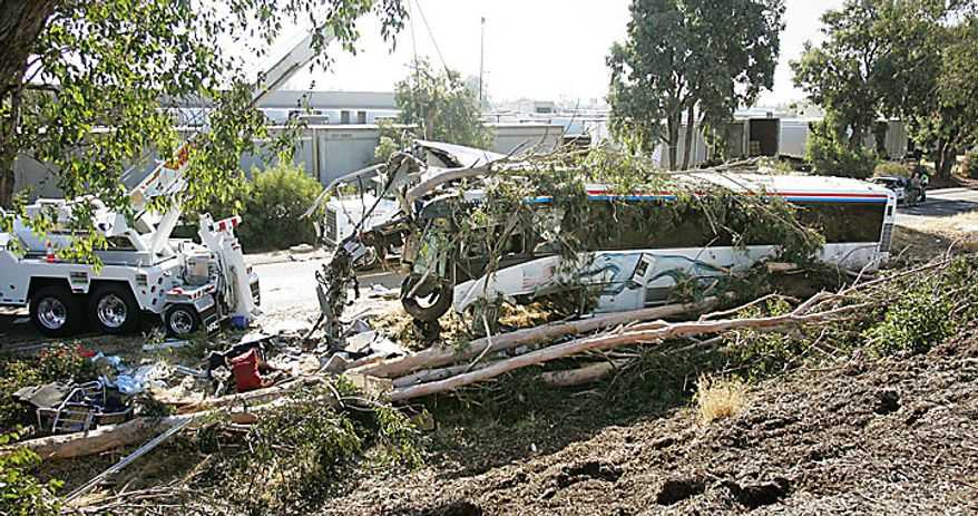 A crane begins to pull a Greyhound Bus that crashed and killed at least six people and injured many others on Thursday, July 22, 2010 in Fresno, Calif. (AP Photo/Gary Kazanjian)