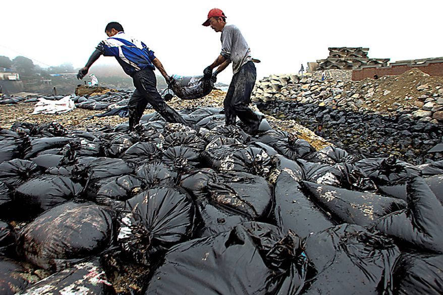 In this photo taken Wednesday, July 21, 2010, workers move a bag on the beach polluted by crude oil after a pipeline explosion in Dalian in northeast China's Liaoning province. China National Petroleum Corp. said Thursday a vital pipeline has resumed operations after the explosion caused the country's largest reported oil spill. (AP Photo)