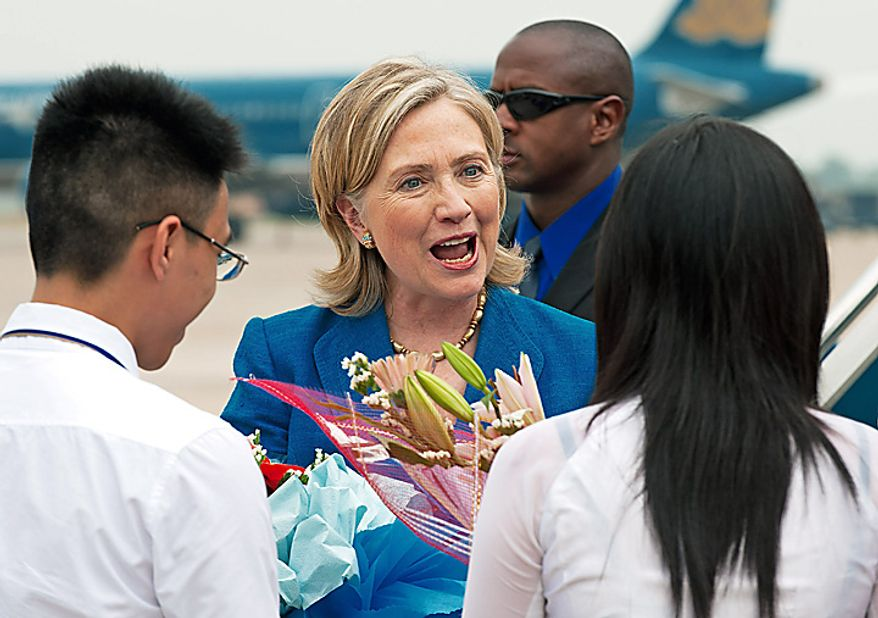 U.S. Secretary of State Hillary Rodham Clinton is greeted with flowers as she arrives at Hanoi Noi Bai International Airport to later meet with Vietnamese officials and attend the ASEAN-US Ministerial Meeting, Thursday, July 22, 2010, in Hanoi, Vietnam. (AP Photo/Paul J. Richards, Pool)
