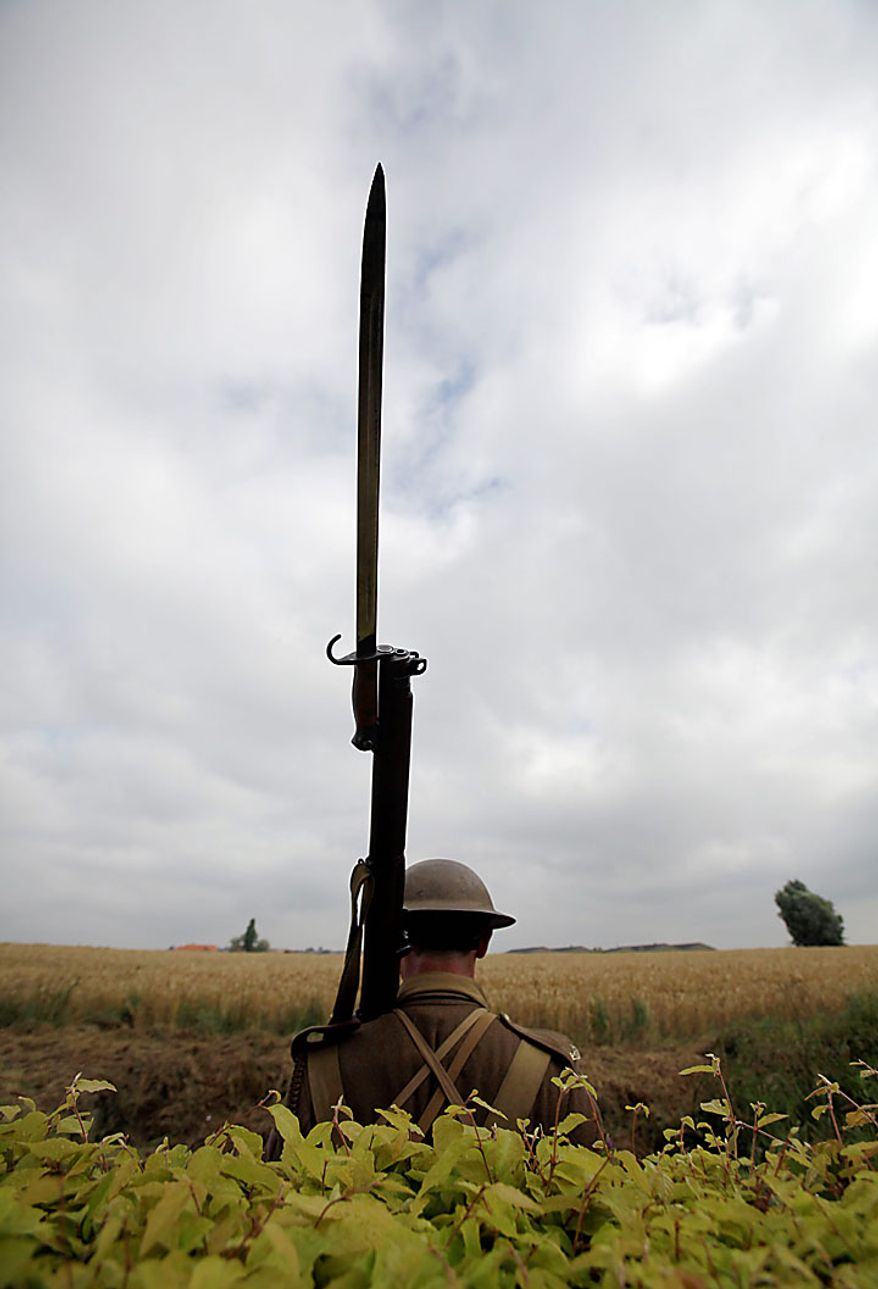 A man dressed in a World War One uniform stands guard outside the Prowse Point Cemetery during a re-burial ceremony for Australian World War One soldier, Private Alan James Mather in Ploegsteert, in Belgium on Thursday, July 22, 2010. Mr. Mather, originally from Invernell, NSW, Australia was one of 216,000 men from Australia, New Zealand and the UK who fought in the Battle of Messines from June 7-14, 1917. The body of Mr. Mather was discovered by a British archeological team in 2008, and further DNA tests by a Belgian laboratory revealed his full identity. (AP Photo/Virginia Mayo)