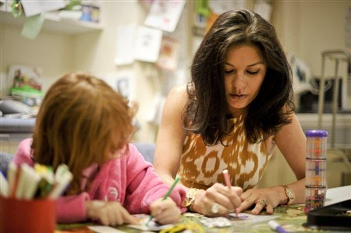 Actress Catherine Zeta Jones plays with Catrin Verdin, aged seven, from Aberavon, Wales, in the children's play room during a visit to the Children's Hospital for Wales in Cardiff, where she and her husband Michael Douglas met staff and children Friday, July 23, 2010. The film star couple appealed for donations to help complete the next stage of work four years after they officially opened the hospital. (AP Photo/Ben Birchall/PA Wire)