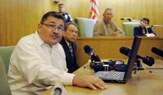 Pedro Carrillo, left, interim city manager of Bell, Calif., announces the resignations of three of Bell's top administrators during a special city council meeting, Thursday, July 22, 2010, in Bell, Calif.  (AP Photo/Chris Pizzello)