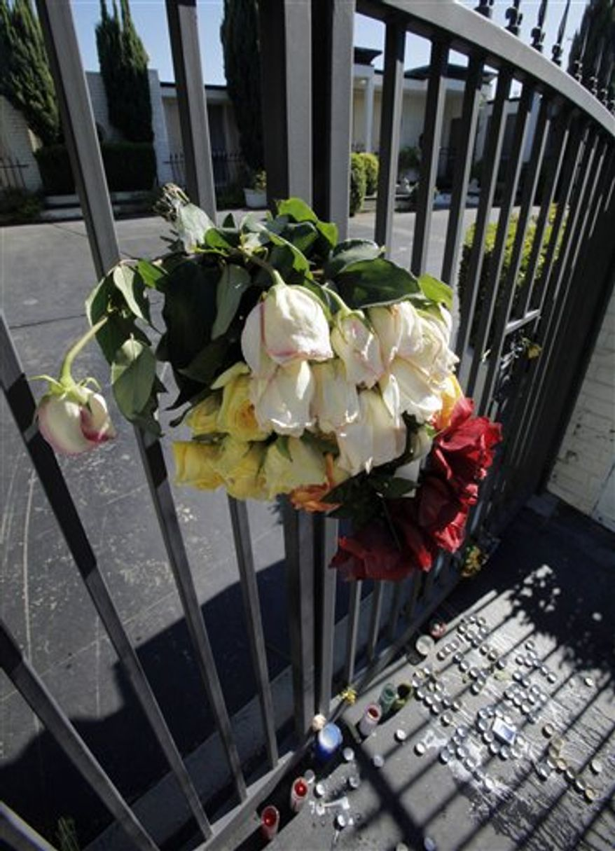 """A bouquet is seen on a gate above a pattern of candles that spell """"RIP TONY T"""" among other memorial items that have been placed outside a home where Katsutoshi """"Tony"""" Takazato was stabbed to death, seen Thursday, July 22, 2010.  Takazato is the son of Japanese movie producer Fuminori Hayashida, who owned the home where Takazato died Tuesday, July 20.  (AP Photo/Reed Saxon)"""
