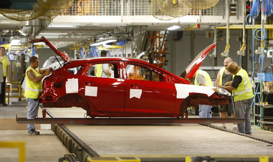 Group leaders work on a pre-production 2012 Ford Focus at the Michigan Assembly Plant in Wayne, Mich., Thursday, July 22, 2010. Ford Motor Co. said Friday, July 23, 2010, it posted net income of $2.6 billion in the second quarter as it continued to grab sales from rivals in a slowly recovering U.S. market. (AP Photo/Carlos Osorio)