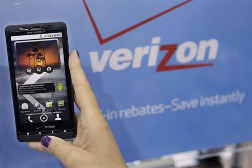 In this July 21, 2010 photo, a Best Buy customer looks at a Motorola Droid phone by Verizon in Mountain View, Calif. Verizon posts a loss for the second quarter Friday, July 23, 2010, due to a buyout for 11,000 workers, and its revenue comes in below Wall Street expectations.(AP Photo/Paul Sakuma)