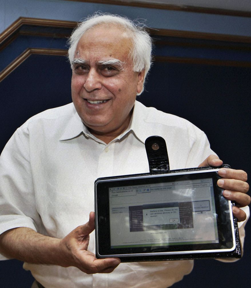 India's Human Resource Development Minister Kapil Sibal displays the prototype of a $35 basic touch-screen tablet computer aimed at students in New Delhi on Thursday, July 22, 2010. The device looks like an iPad and is 1/14th the cost. India hopes to bring the computer into production by 2011. (AP Photo)