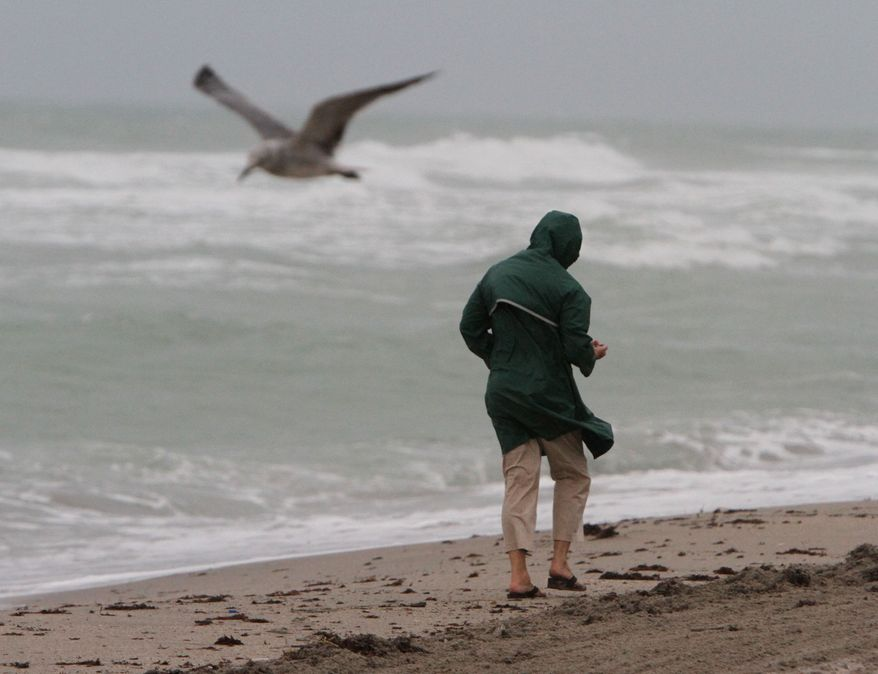 "Magva Balbuena walks on the Hollywood beach Friday, July 23, 2010, looking for a ""lucky sea bean"" she says are considered lucky in Cuba, where she is from. Rainy and windy weather are expected as Tropical Storm Bonnie heads through Florida. (AP Photo/The Miami Herald, Walter Michot)"