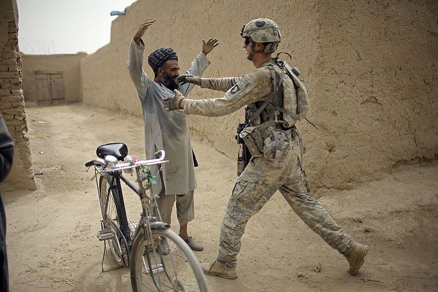 A U.S. Army soldier frisks an Afghan villager during a patrol by the 1-320th Alpha Battery, 2nd Brigade of the 101st Airborne Division near COP Nolen, in the volatile Arghandab Valley, Kandahar, Afghanistan, Friday, July 23, 2010. (AP Photo/Rodrigo Abd)