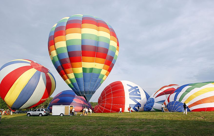 People inflate hot air balloons early Friday, July 23, 2010, at the Quick Chek New Jersey Festival of Ballooning in Readington, N.J. The festival runs through Sunday, July 25, 2010. (AP Photo/ Mel Evans)