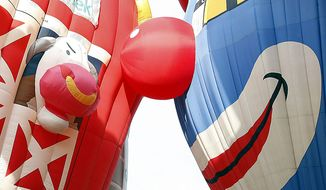 A cow and a clown come face to face as hot air balloons are inflated at the Quick Chek New Jersey Festival of Ballooning, Friday, July 23, 2010, in Readington, N.J. The festival runs through Sunday, July 25, 2010. (AP Photo/ Mel Evans)