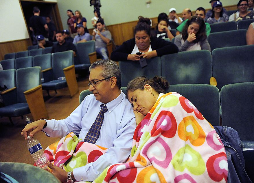 Coco Ceja, right, of Bell, Calif., falls asleep on the shoulder of her husband Marcelino as they wait to hear from city officials following a lengthy closed-door meeting of the Bell City Council, Thursday, July 22, 2010, in Bell, Calif. Revelations about Bell city leaders' pay has sparked anger in a blue-collar town that is one of the poorest in Los Angeles County. Bell's police chief and two top city administrators agreed to resign Thursday night during the closed-door meeting. (AP Photo/Chris Pizzello)