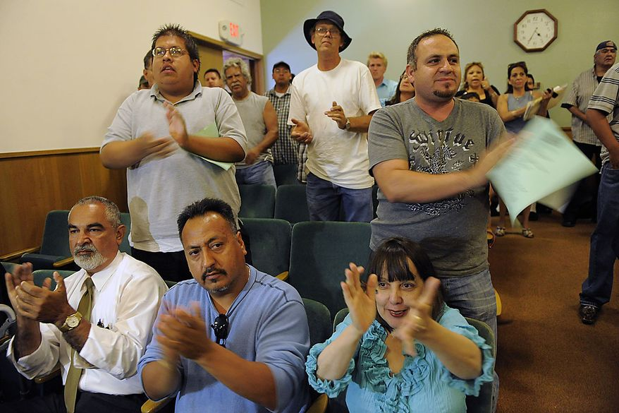 Bell city residents applaud a speaker during a special Bell City Council meeting to consider firing the police chief and two top administrators, Thursday, July 22, 2010, in Bell, Calif. Revelations about Bell city leaders' pay has sparked anger in a blue-collar town that is one of the poorest in Los Angeles County. (AP Photo/Chris Pizzello)