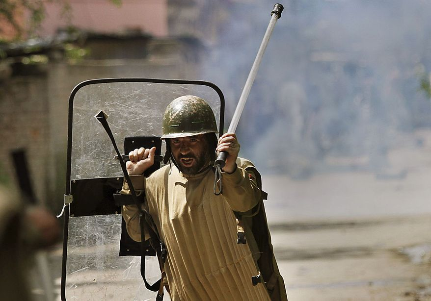 An Indian policeman gestures to his colleagues to move ahead  during a protest in Srinagar, India, Friday, July 23, 2010. The predominantly Muslim region, where resistance to rule by Hindu-majority India is strong, has witnessed curfews and strikes for nearly a month after anti-India street protests and clashes surged. Residents accuse government forces of killing at least 17 people, mostly teenagers, in the demonstrations. (AP Photo/ Dar Yasin)