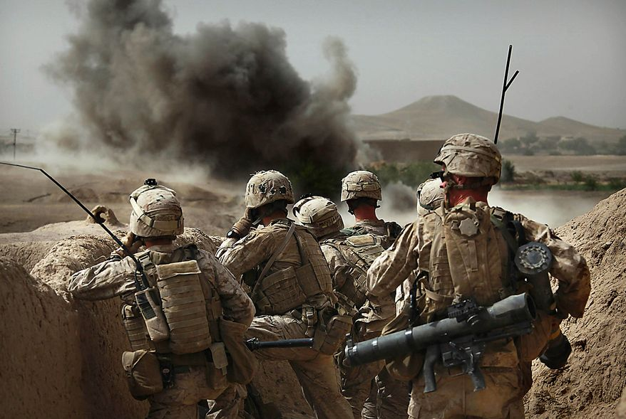 United States Marines from Bravo Company of the 1st Battalion of the 2nd Marines watch the explosion after calling in an airstrike during a gunbattle as part of an operation to clear the area of insurgents near Musa Qaleh, in northern Helmand Province, southern Afghanistan, Friday, July 23, 2010. (AP Photo/Kevin Frayer)