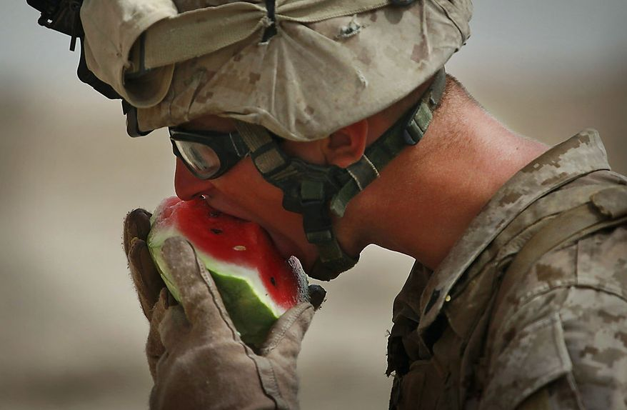 United States Marine Cpl. Ryan Farris from Bravo Company of the 1st Battalion of the 2nd Marines eats watermelon following a gunbattle as part of an operation to clear the area of insurgents near Musa Qaleh, in northern Helmand Province, southern Afghanistan, Friday, July 23, 2010. (AP Photo/Kevin Frayer)