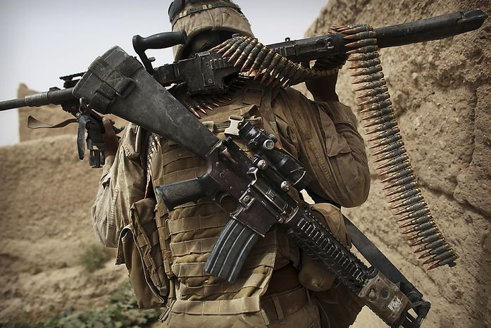 A United States Marine from Bravo Company of the 1st Battalion of the 2nd Marines carries his weapons and ammunition during an operation to clear the area of insurgents near Musa Qaleh, in northern Helmand Province, southern Afghanistan, Friday, July 23, 2010. (AP Photo/Kevin Frayer)
