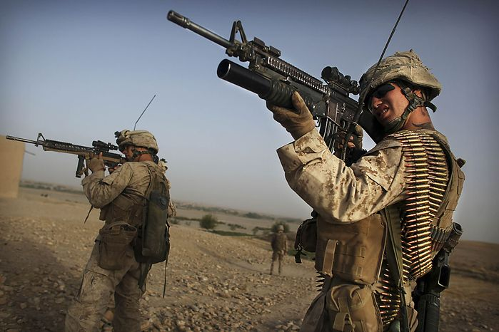 United States Marine LCpl. Steven Paratore, right, and an unidentified colleague from Bravo Company of the 1st Battalion of the 2nd Marines fires a machine gun scan the horizon for militants as part of an operation to clear the area of insurgents near Musa Qaleh, in northern Helmand Province, southern Afghanistan, Friday, July 23, 2010. (AP Photo/Kevin Frayer)