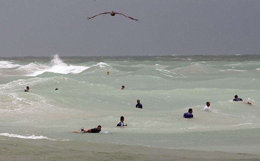 An American Brown Pelican flies past surfers waiting for a wave, Friday, July 23, 2010 near Haulover Beach Park in Miami-Dade County, Fla. A tropical storm warning has been issued for the Gulf coast as Tropical Storm Bonnie begins moving over South Florida. (AP Photo/Wilfredo Lee)