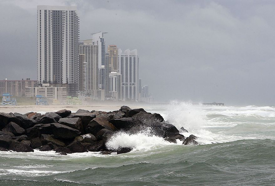Waves crash over rocks, Friday, July 23, 2010 in Baker's Haulover Inlet in front of buildings in Sunny Isles Beach, Fla. A tropical storm warning has been issued for the Gulf coast as Tropical Storm Bonnie begins moving over South Florida. (AP Photo/Wilfredo Lee)