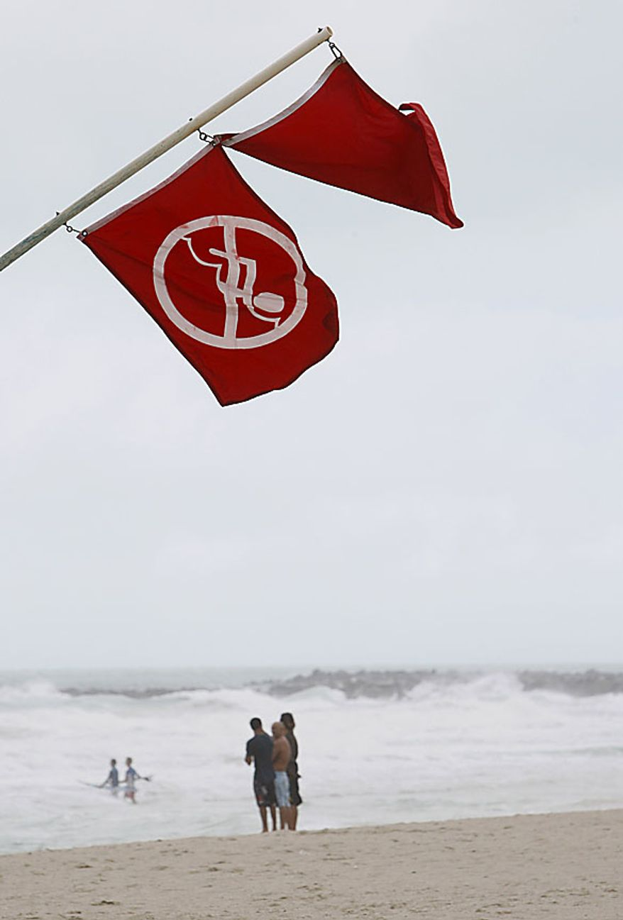 No swimming and hazard flags fly from a lifeguard station as beach goers stand on the shore watching surfers Friday, July 23, 2010 on Miami Beach, Fla. A tropical storm warning has been issued for the Gulf coast as Tropical Storm Bonnie begins moving over South Florida. (AP Photo/Wilfredo Lee)