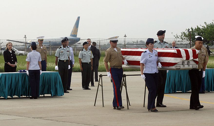 The U.S. military personnel carry a casket containing remains which is believed to be the U.S. servicemen, missing in action during the Vietnam War as U.S. Secretary of State Hillary Rodham Clinton witnesses during a repatriation ceremony at the airport in Hanoi, Friday, July 23, 2010. (AP Photo/Kham, Pool)