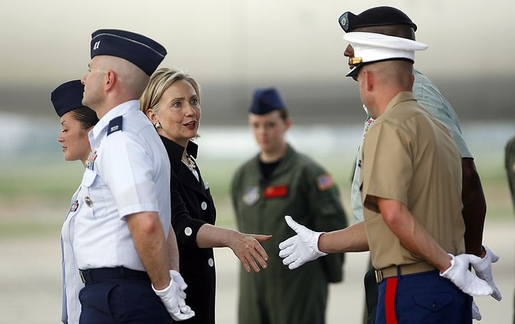 U.S. Secretary of State Hillary Rodham Clinton, center, greets U.S. military personnel during a repatriation ceremony for the remains of  the U.S. servicemen, missing in action during the Vietnam War at the airport in Hanoi, Friday, July 23, 2010. (AP Photo/Kham, Pool)