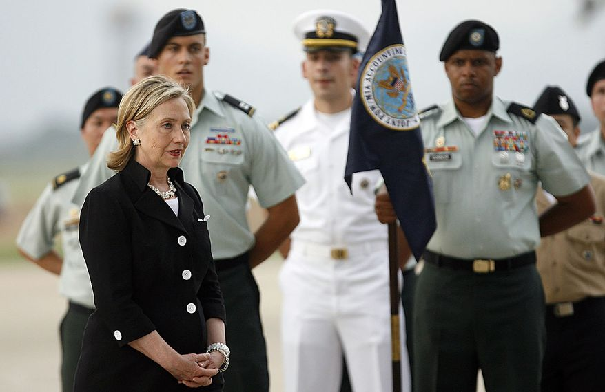 U.S. Secretary of State Hillary Rodham Clinton, left, speaks with U.S. military personnel during a repatriation ceremony for the remains of the U.S. servicemen who were missing in action during the Vietnam War at the airport in Hanoi, Friday, July 23, 2010.  (AP Photo/Kham, Pool)