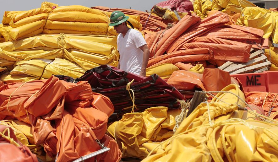 A worker prepares to secure cleaned and repaired oil retention booms at a staging area in Grand Isle, La., Friday, July 23, 2010. Tropical Storm Bonnie is expected to make landfall sometime Saturday along the Louisiana coast. BP has recalled much of the oil skimming efforts in anticipation of bad weather. (AP Photo/Dave Martin)