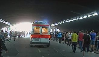"In this image taken from television an ambulance at the scene where people receive first aid after a panic on this year's techno-music festival ""Loveparade 2010"" in Duisburg, Germany, on Saturday, July 24, 2010. More than a dozen people were killed and others injured when mass panic broke out in a tunnel at the Love Parade. (AP Photo/WIEBOLD TV via APTN)"