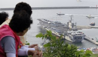 "South Koreans watch the Nimitz-class USS George Washington leaving for joint military exercises at the Busan port in Busan, south of Seoul, South Korea, Sunday, July 25, 2010. The massive nuclear-powered U.S. supercarrier began maneuvers Sunday with ally South Korea in a potent show of force that North Korea has threatened could lead to ""sacred war."" (AP Photo/ Lee Jin-man)"