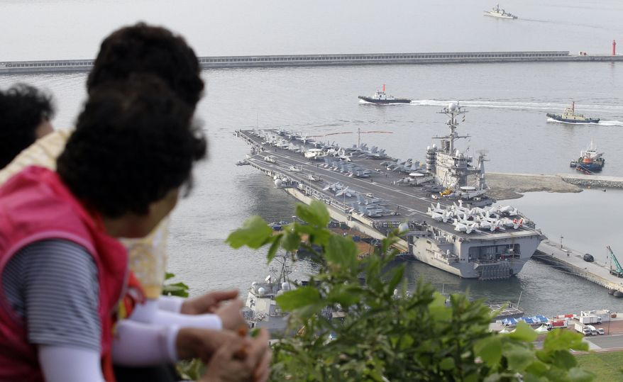 """South Koreans watch the Nimitz-class USS George Washington leaving for joint military exercises at the Busan port in Busan, south of Seoul, South Korea, Sunday, July 25, 2010. The massive nuclear-powered U.S. supercarrier began maneuvers Sunday with ally South Korea in a potent show of force that North Korea has threatened could lead to """"sacred war."""" (AP Photo/ Lee Jin-man)"""