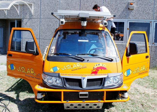 A technician works on an unmanned electric-powered vehicle in Parma, Italy. Next week, four electric-powered orange vans depart on what has been conceived as the longest-ever test drive of unmanned vehicles: an 8,000-mile, three-month road trip from Italy to China. (Associated Press)